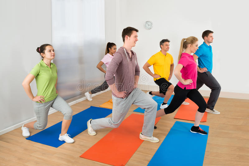 Group Of People Exercising On Mat stock photos