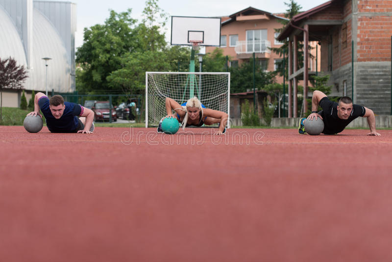Group Of People Exercising Push-Ups On Medicine Ball stock photo