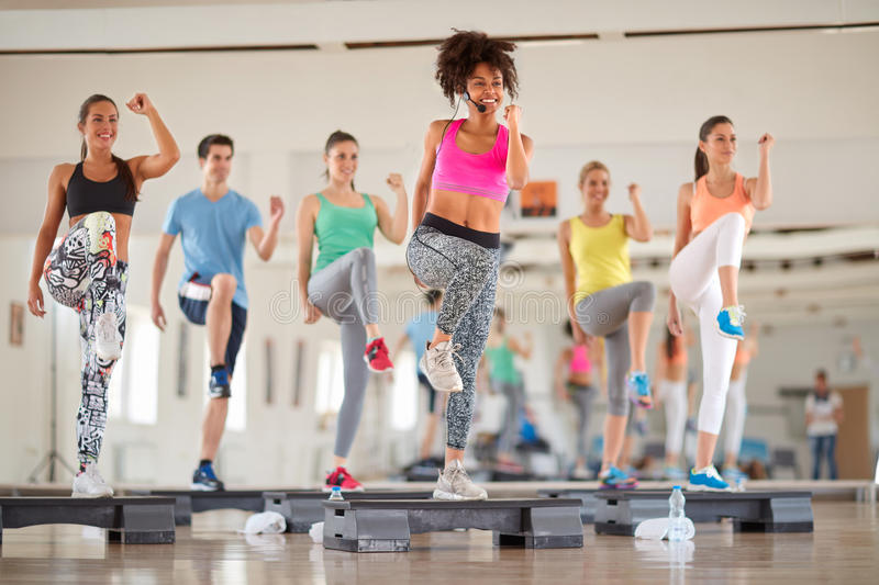 Group of people exercising on stepper. Young group of people exercising on stepper at gym royalty free stock photos