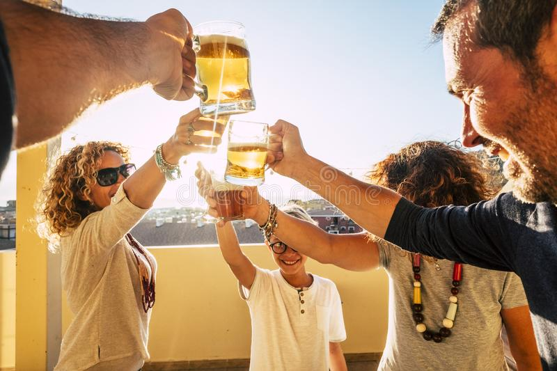 Group of people families and friends having fun together clinking with beers and orange juice - friendship celebrating event in. Outdoor terrace at home royalty free stock photos