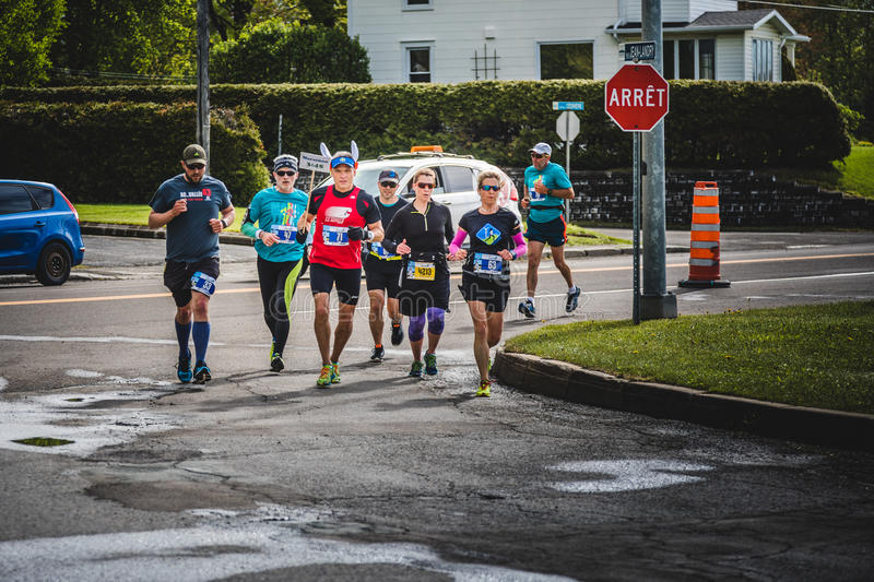 Group of People Following the Rabbit Leader during the Marathon. CARLETON, CANADA - June 4, 2017. During the 5th Marathon of Carleton in Quebec, Canada. Group of royalty free stock photo