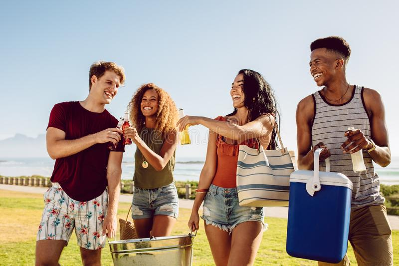 Group of people going on beach party. Group of people carrying cooler and beverage tub for party on beach. Diverse group of young people walking outdoors and stock image