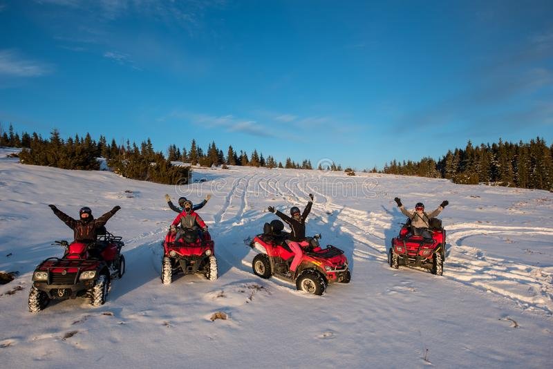 Group of people with hands up on four-wheelers ATV bikes in the the mountains in winter evening. Group of people sitting with hands up on four-wheelers ATV bikes stock photos