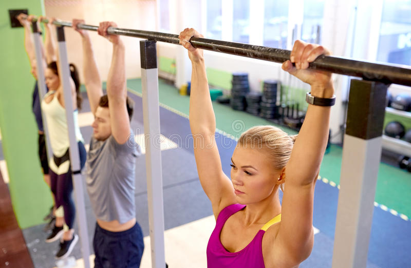 Group of people hanging at horizontal bar in gym. Sport, fitness, exercising and people concept - women with heart-rate tracker hanging on horizontal bar at royalty free stock photography