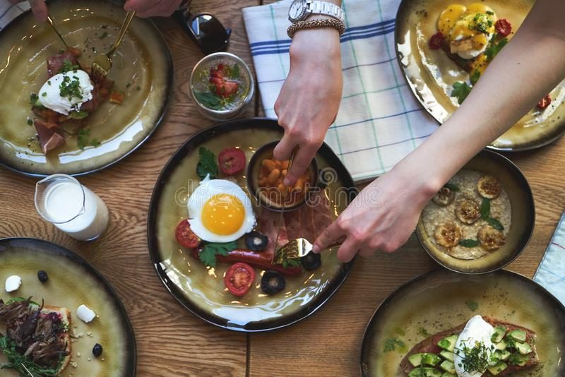 Group of people having breakfast and sitting at table, top view. Friends group having english breakfast at cafe restaurant, close-up stock photo