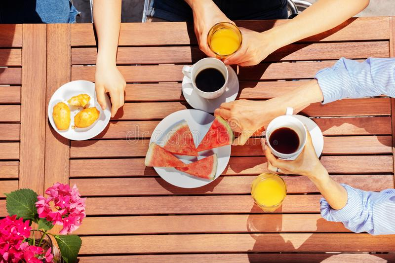 Group of people having breakfast together outdoors stock photo