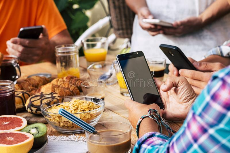 Group of people having breakfast on a wooden table full of food and everbody use the mobile phone internet connection - modern. Addicted society and technology royalty free stock image