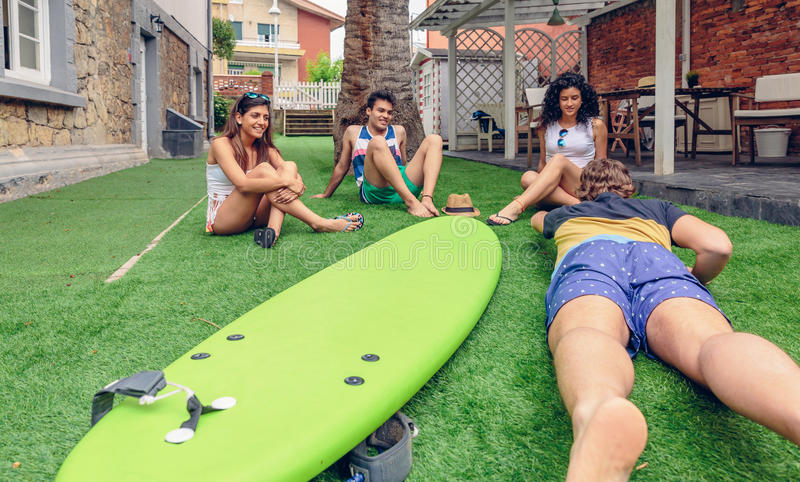 Group of people having fun in a surf class. Group of young people having fun in a summer surf class outdoors. Holidays leisure concept royalty free stock photography