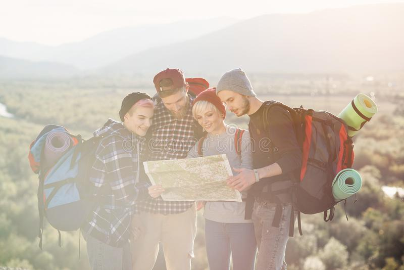 Group of people hiking and looking at map during their adventure. Two men and two women, hikers exploring mountains stock photos