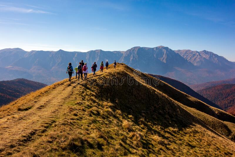 Group of people hiking in the mountains during autumn season royalty free stock photography