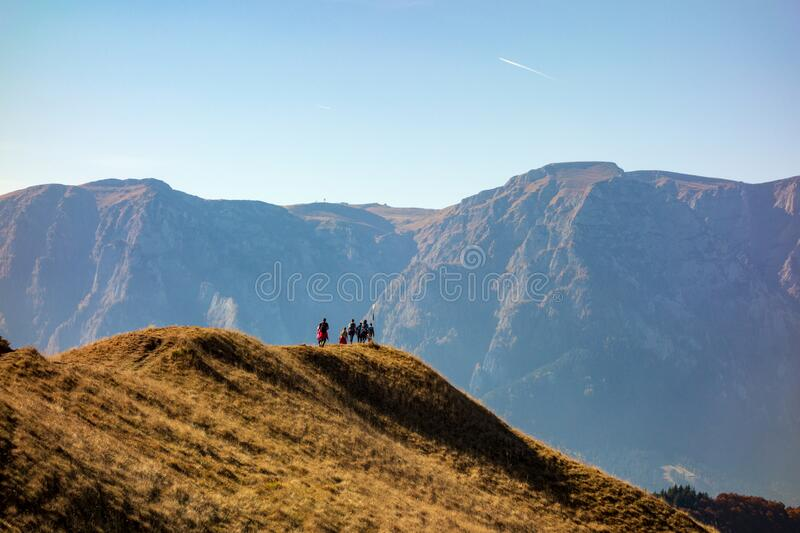 Group of people hiking in the mountains during autumn season stock photo