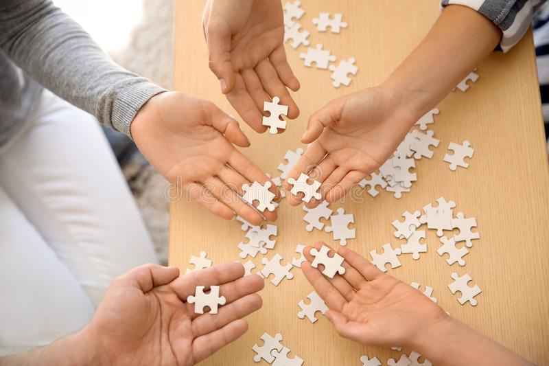 Group of people holding pieces of puzzle over wooden table stock photography