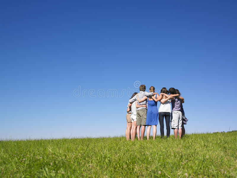 Group of People in Huddle in Field. A group of people huddle in a field. Horizontally framed shot stock photography
