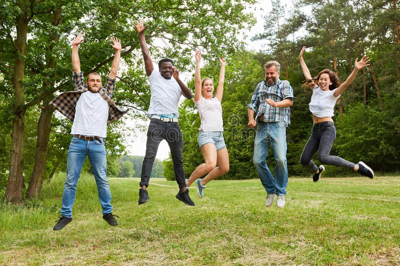 Group of people while jumping in the nature. Happy multicultural group of people while jumping in the nature stock photos