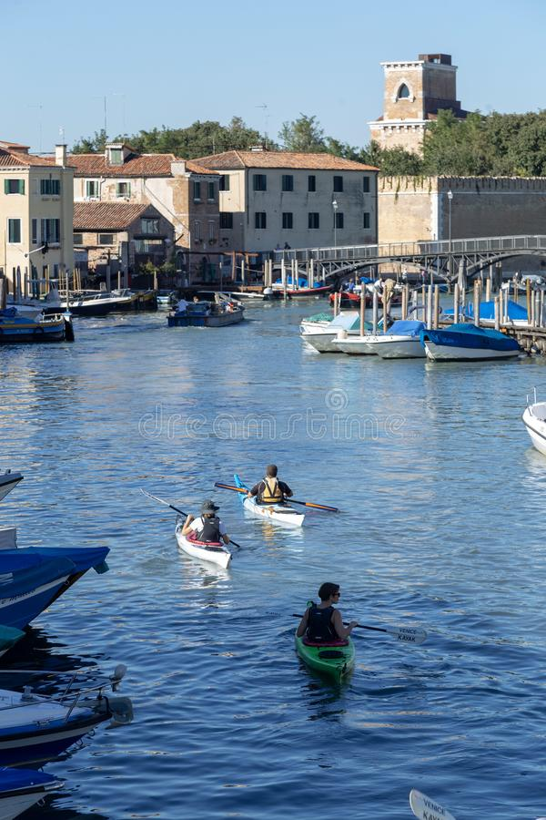 People kayaking in the Venetian canal. Venice, Italy. Group of people kayaking in the Venetian canals. Venice, Italy royalty free stock images