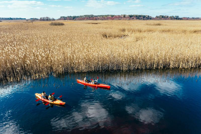 Group of people in kayaks among reeds on the autumn river. royalty free stock images