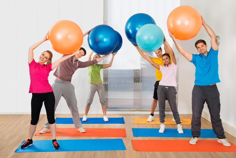 Group Of People Lifting Pilates Ball stock photo