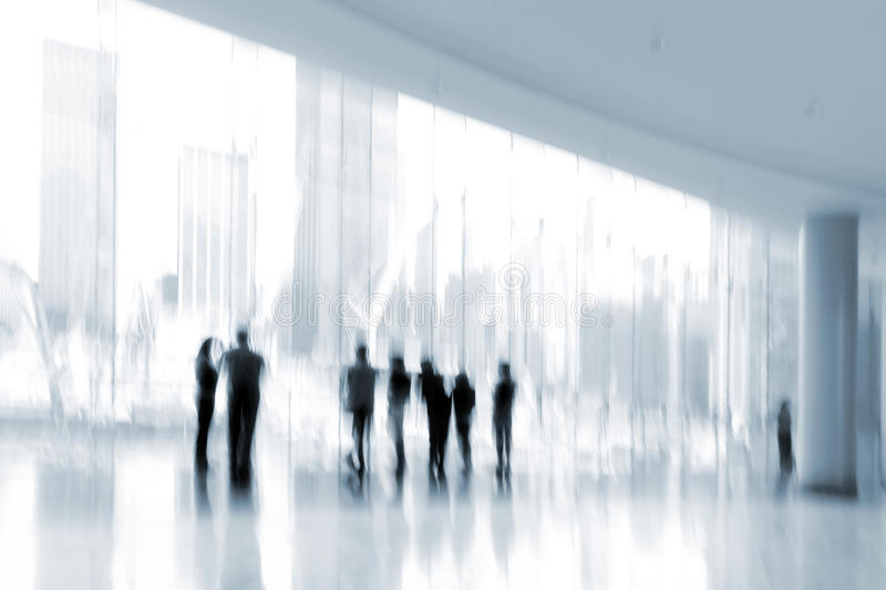Group of people in the lobby business center and blue tonality. Abstract image of people in the lobby of a modern business center with a blurred background and royalty free stock photography