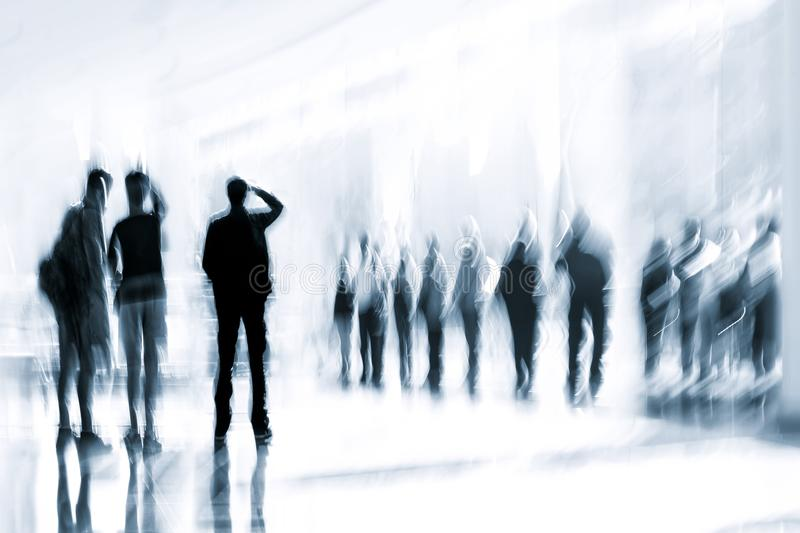 Group of people in the lobby business center and blue tonality. Abstract image of people in the lobby of a modern business center with a blurred background and stock photos