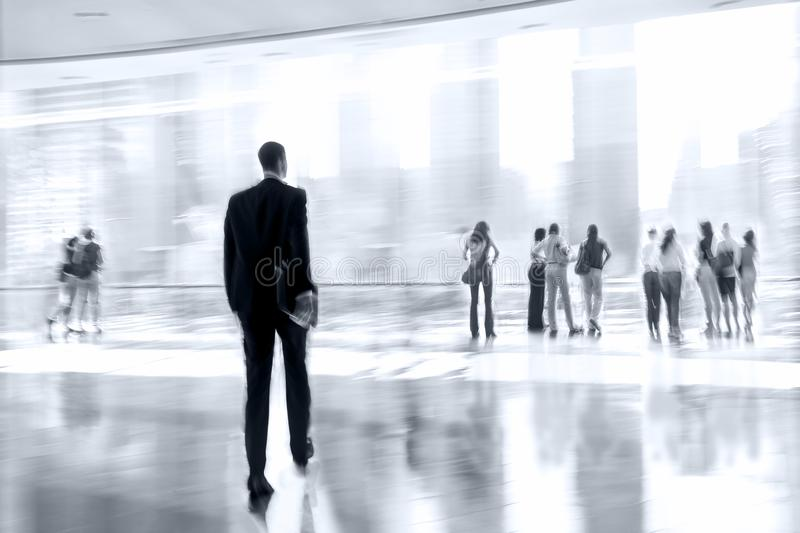 Group of people in the lobby business center in monochrome blue stock image