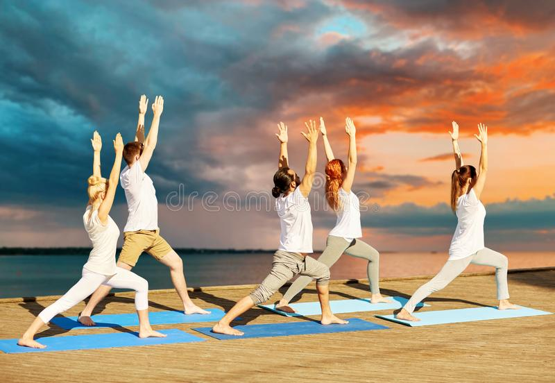Group of people making yoga exercises outdoors stock images