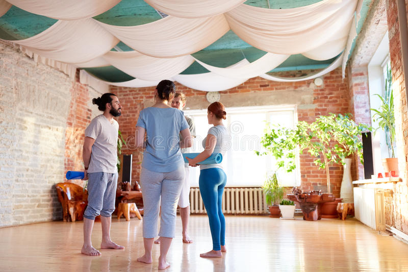 Group of people with mats at yoga studio or gym royalty free stock photography