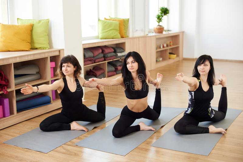 Group of people meditation making sitting yoga pose in luxury fitness center. Women practicing asana called pigeon pose stock image
