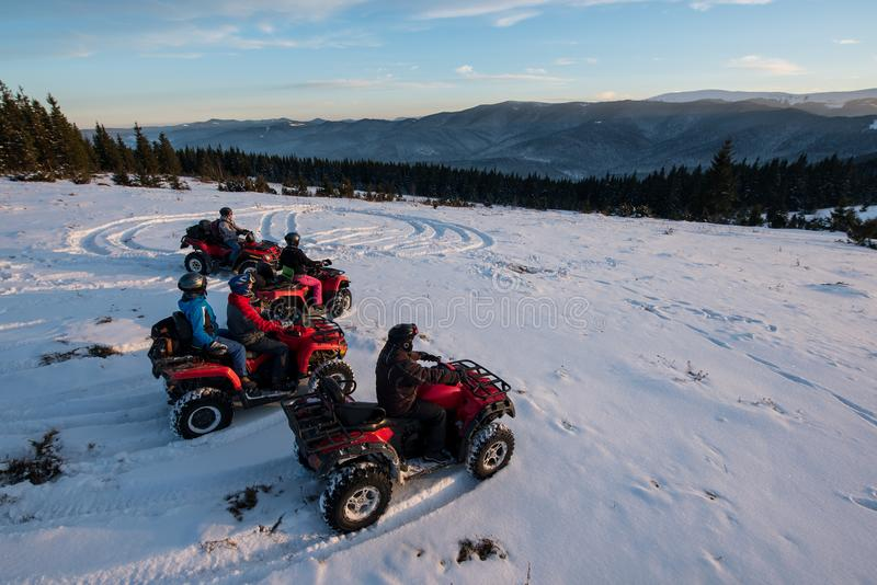 Group of people on off-road four-wheelers ATV bikes in the the mountains in winter evening. Group of people sitting on off-road four-wheelers ATV bikes in the stock photos