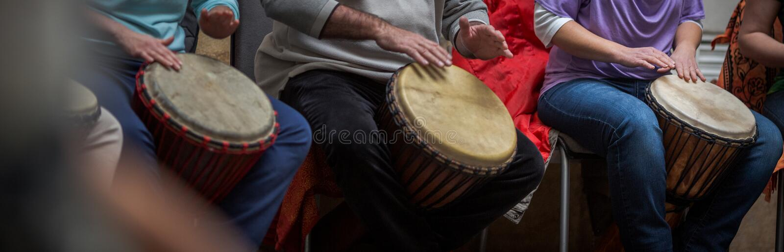 Group of people playing on drums stock image