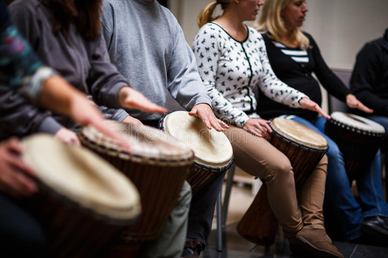 Group of people playing on drums royalty free stock photography