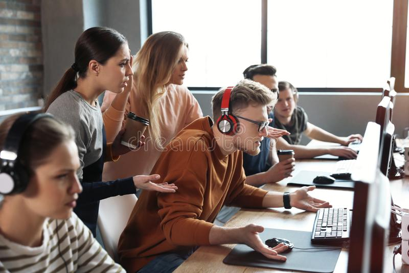 Group of people playing video games in cafe. Group of people playing video games in internet cafe stock image