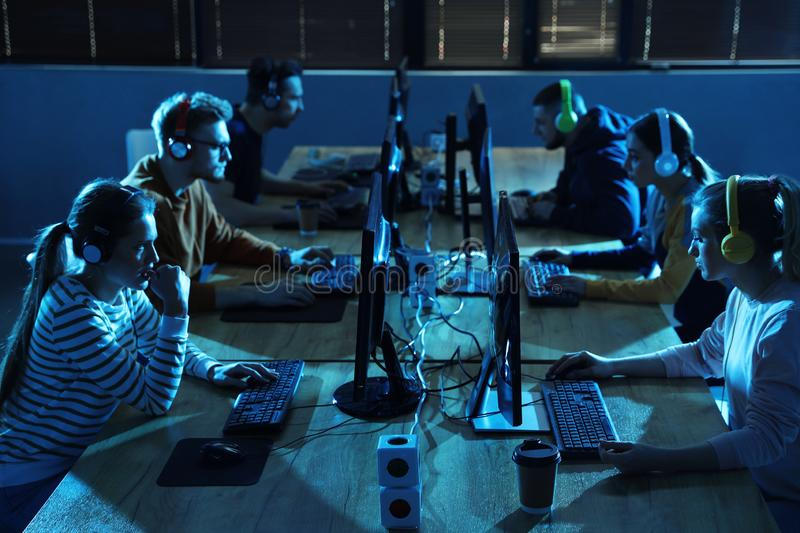 Group of people playing video games in cafe. Group of people playing video games in internet cafe royalty free stock images