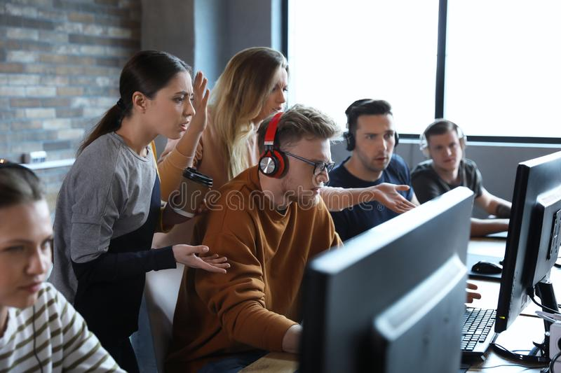 Group of people playing video games in cafe. Group of people playing video games in internet cafe stock photography