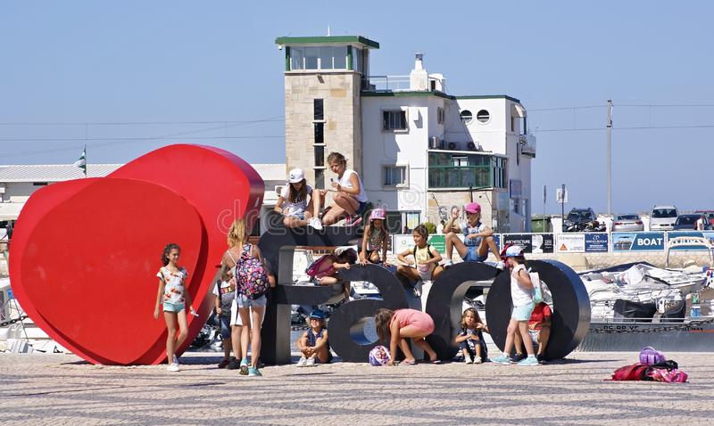 People sitting in front of the Faro sign, Algarve - Portugal royalty free stock images