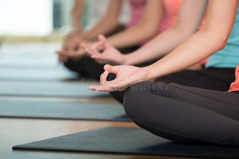 Group of people practicing yoga class, hands closeup background, sport and healthy lifestyle, wellness, well being royalty free stock image