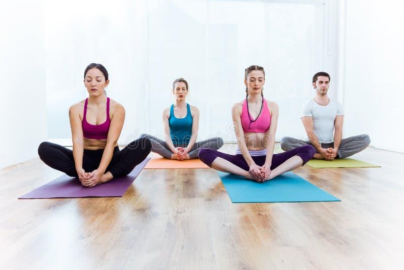 Group of people practicing yoga at home. Baddha Konasana pose. stock photo