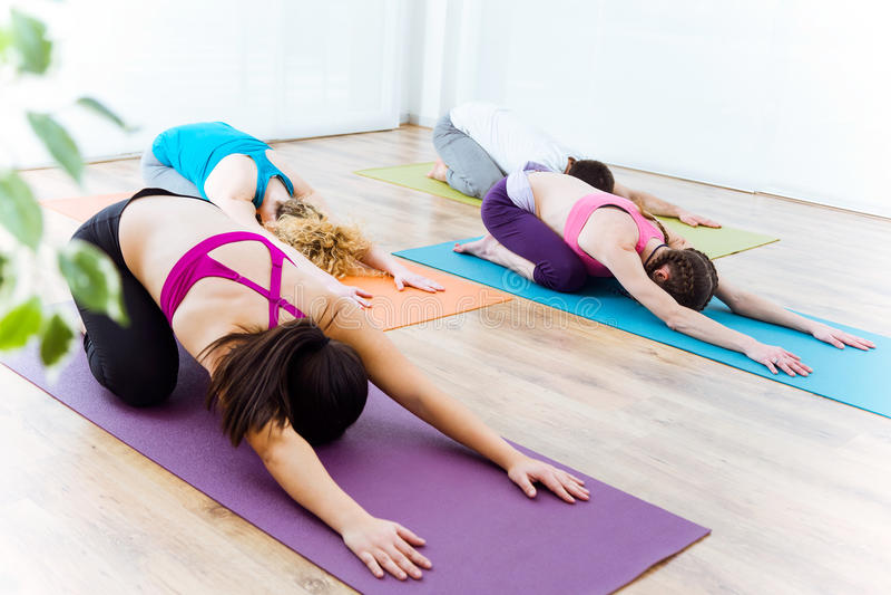 Group of people practicing yoga at home. Balasana pose. stock images