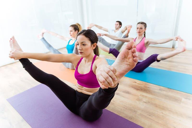 Group of people practicing yoga at home. Upavistha konasana pose royalty free stock photo