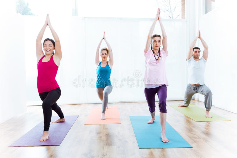 Group of people practicing yoga at home. Virabhadrasana pose. royalty free stock images