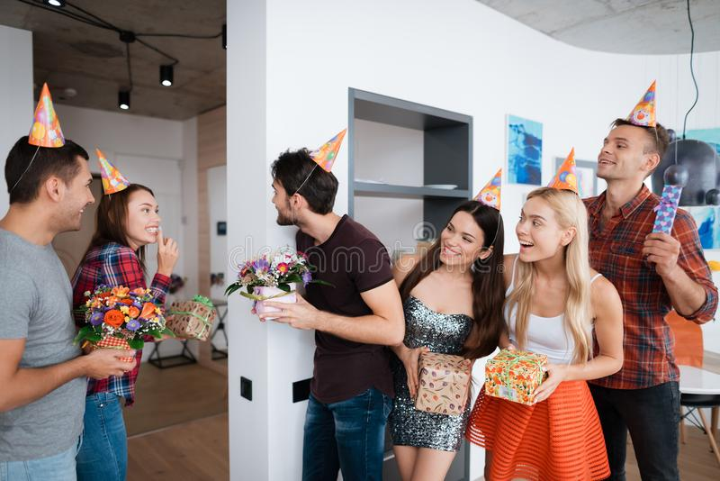 Group of people is preparing a surprise for the birthday girl. They are waiting for her with gifts. royalty free stock photography