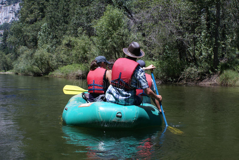 Group of People Rafting Down the River. A group of people on a raft wearing life jackets or vest paddling down the Merced River in Yosemite National Park in stock image