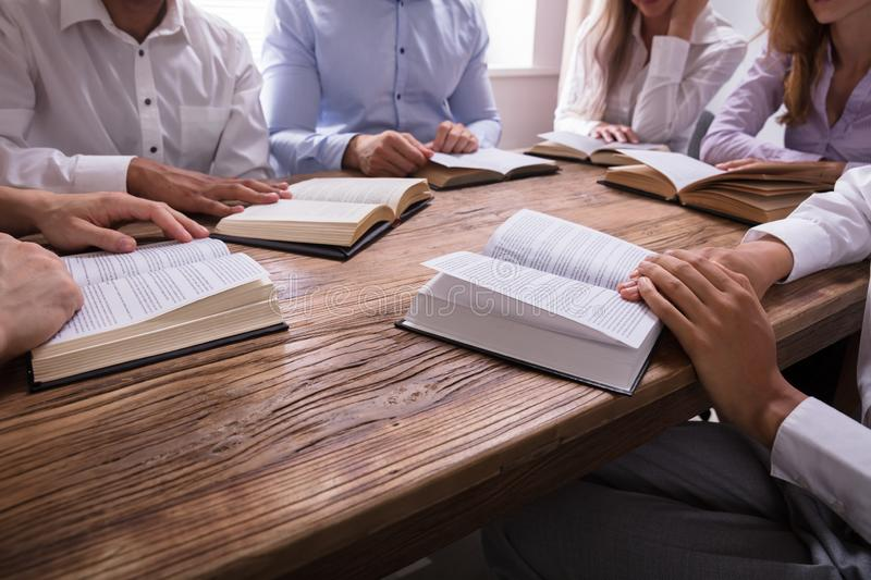Group Of People Reading Bible. On Wooden Desk royalty free stock photography