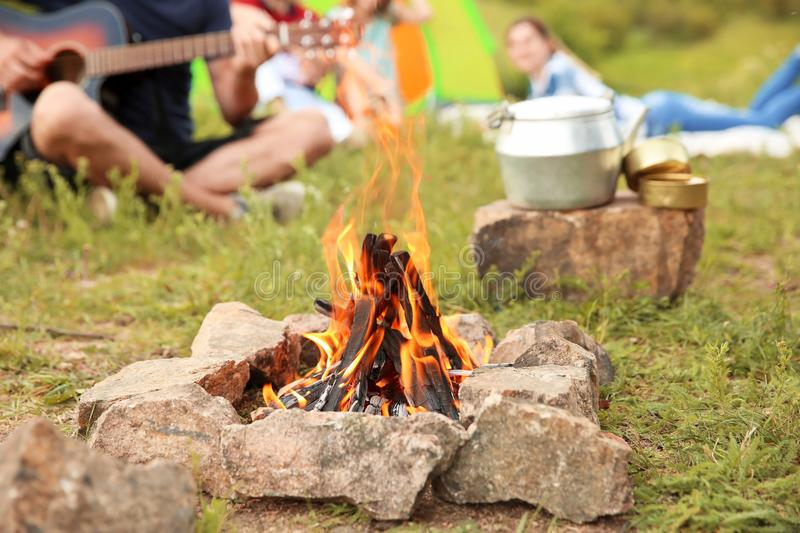 Group of people resting outdoors, focus on bonfire. Camping season royalty free stock image