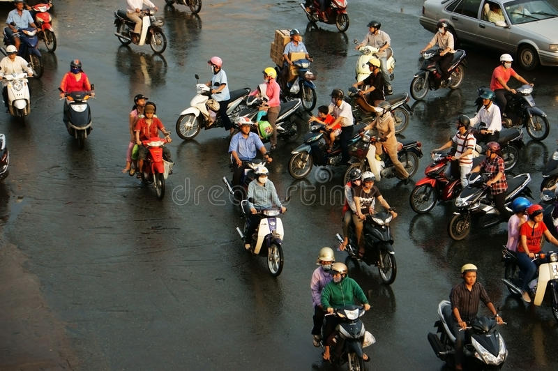 Group of people ride motorbike in rush hour. HO CHI MINH, VIET NAM, ASIA- NOV 22: Group of people wear helmet, ride motorbike moving on street in rush hour, they stock images