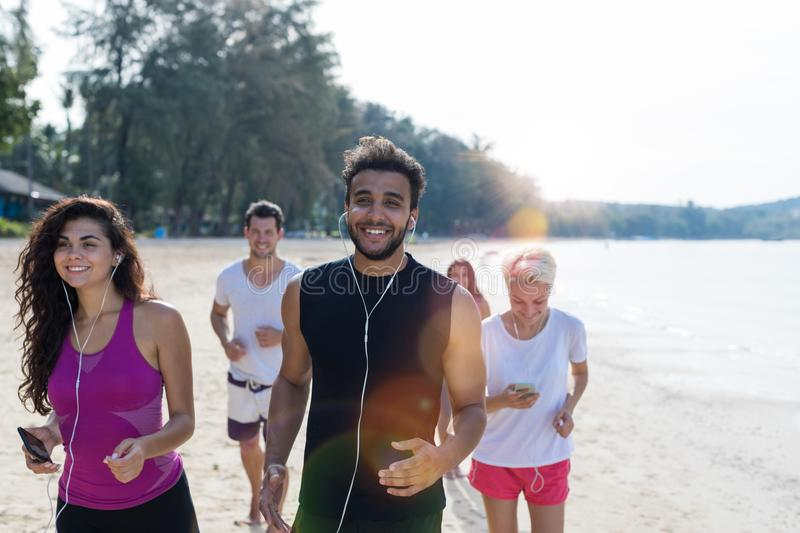 Group Of People Running, Young Sport Runners Jogging On Beach Working Out Smiling Happy, Fit Male And Female Joggers stock images