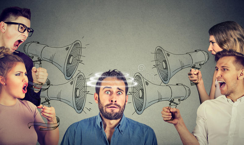 Group of people screaming in megaphones at scared guy. Group of people screaming in megaphones at scared young guy royalty free stock images