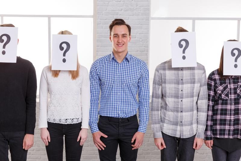 A group of people with sheets with question marks on their faces except for a guy with a close-up smile. A group of people with sheets with question marks on royalty free stock photos