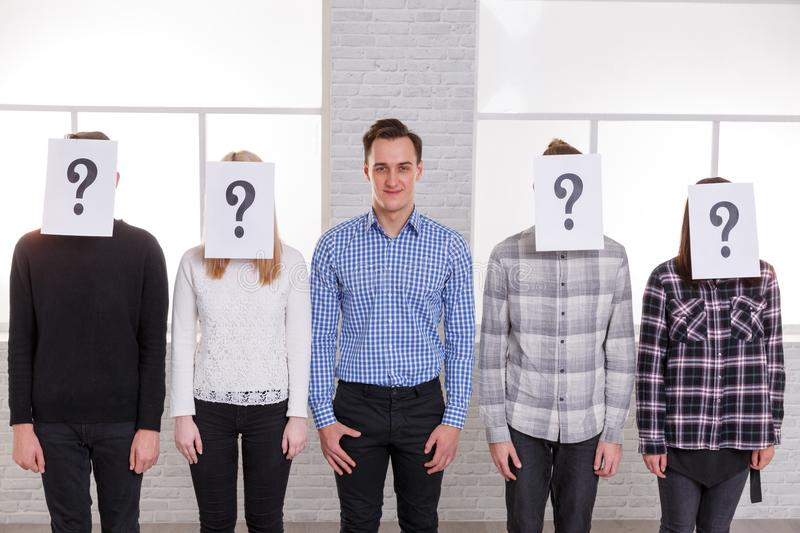 A group of people with sheets with question marks on their faces except a guy with a smile. A group of people with sheets with question marks on their faces stock photography