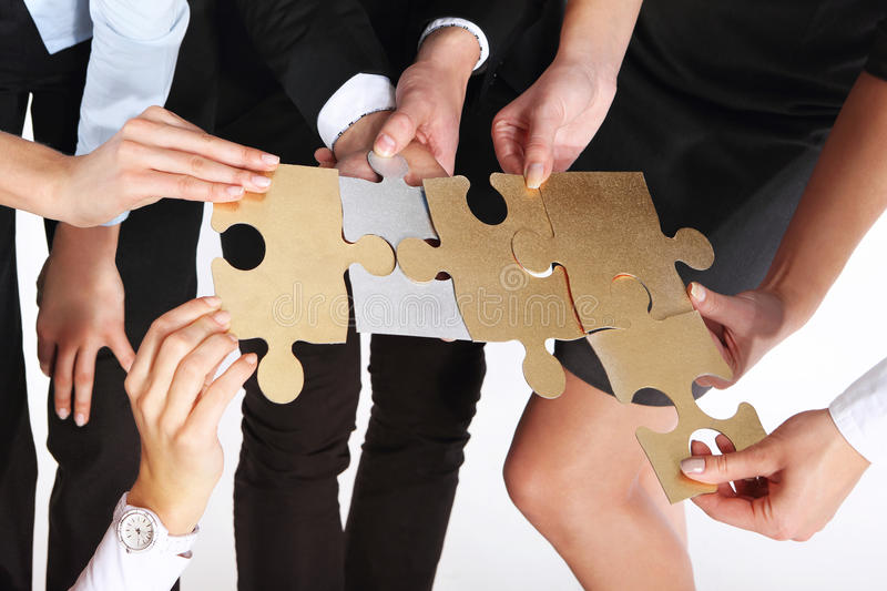 Group of people with silver gold puzzles. royalty free stock image
