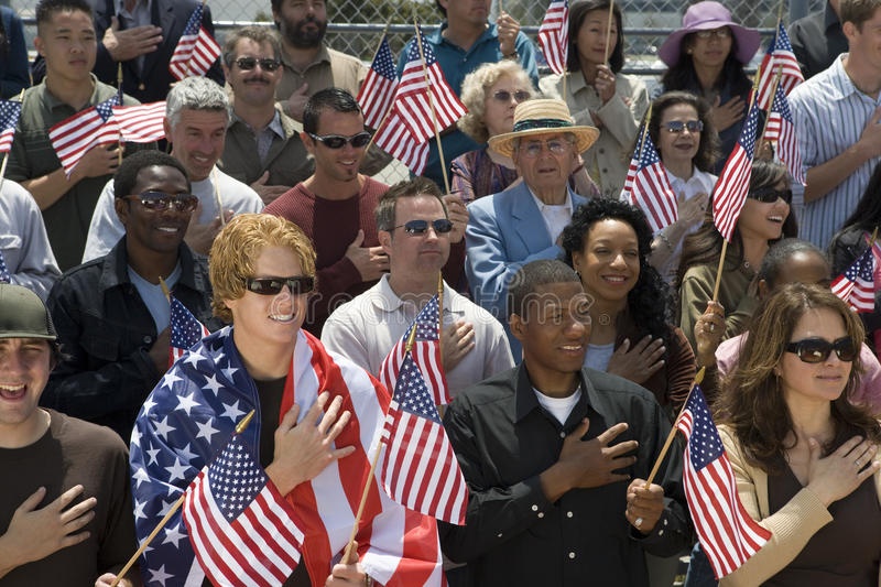 Group Of People Singing American National Anthem. Group of multiethnic people singing American national anthem and holding American flags royalty free stock photo